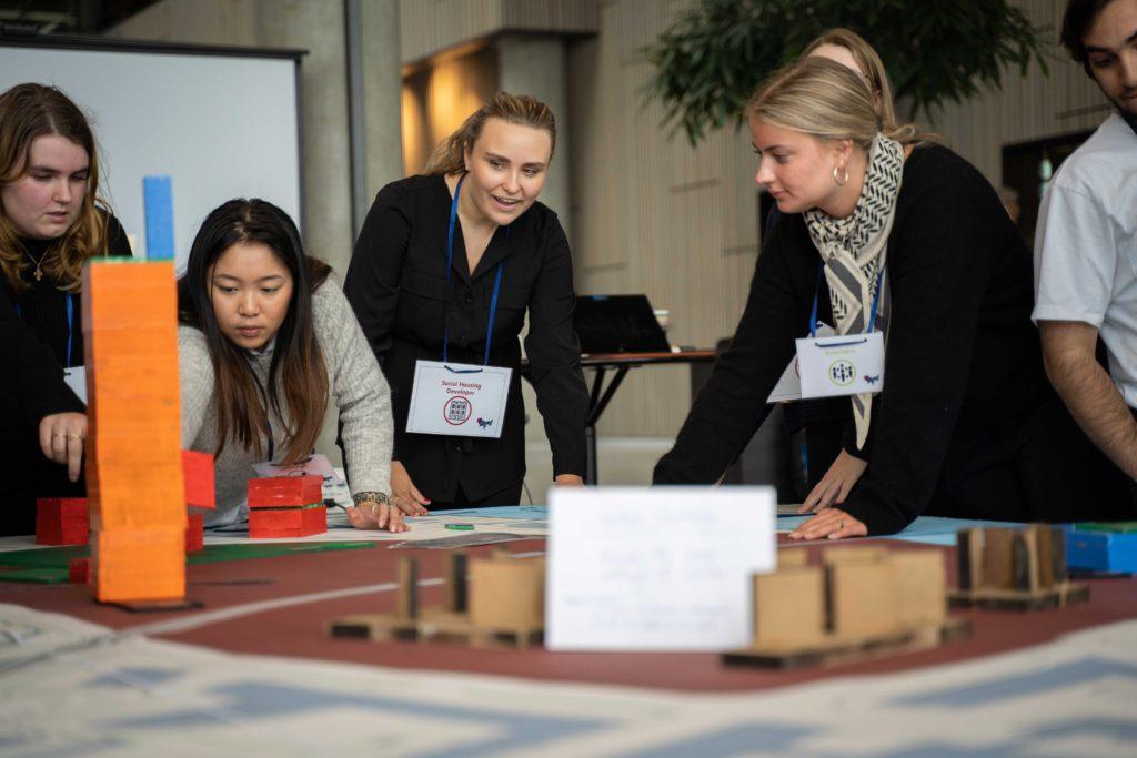 Studerende arbejder ved et stort bord med forskellige kasser, papirer mm.